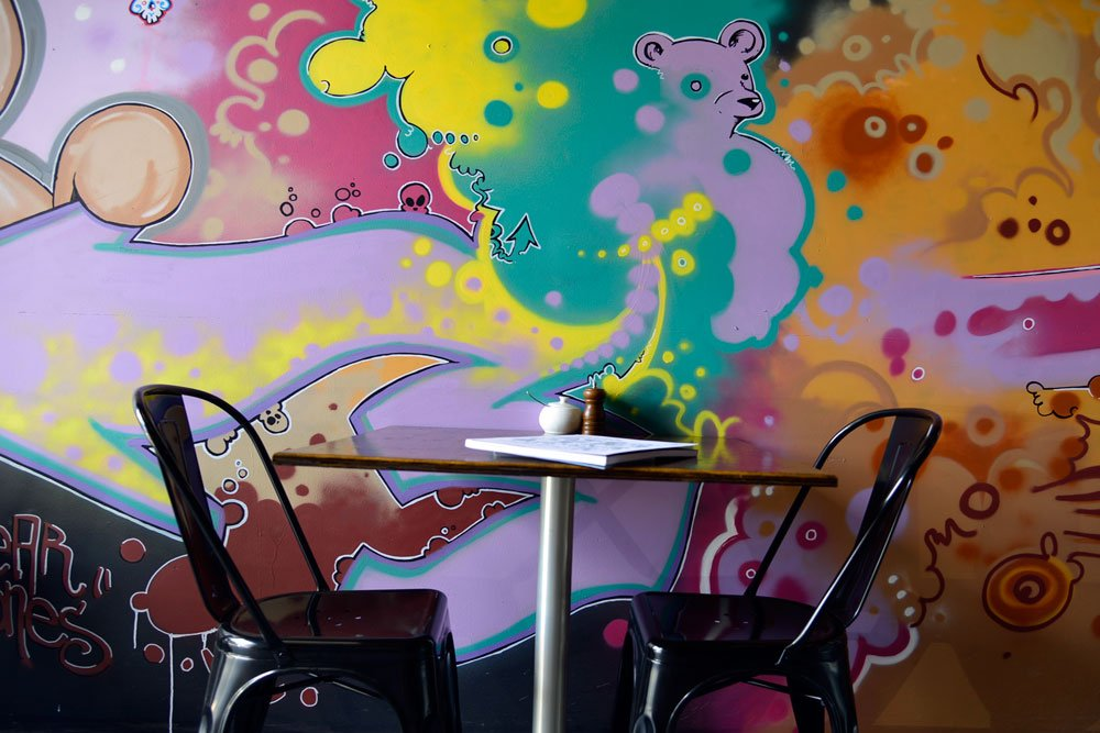 Seating and stencil art in the Bear Bones Espresso cafe in Fortitude Valley