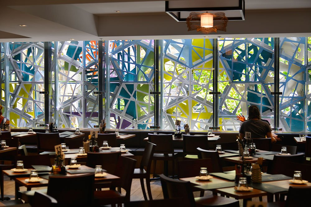 Seating inside main dining room looking out to Wintergarden's outdoor sculpture mural