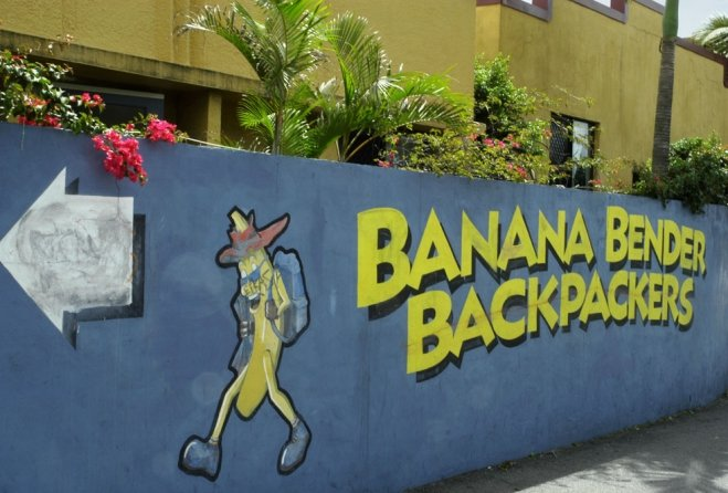 Sign painted on wall with banana carrying a backpack pointing to Banana Benders Backpackers
