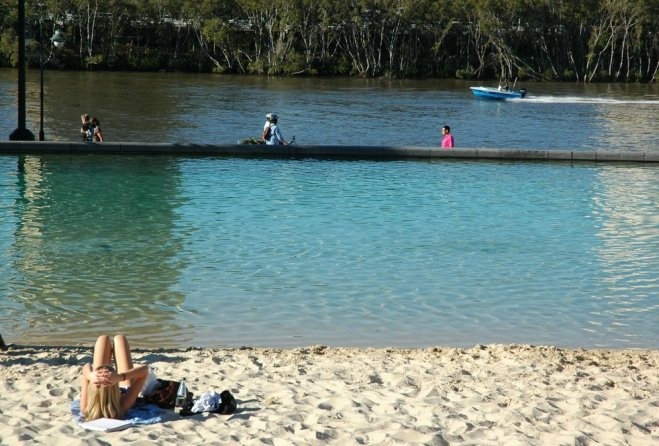 Woman lying on Streets Beach looking at speed boad on Brisbane River and mangroves.