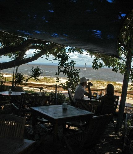 Couple looking out to sea from restaurant's covered terrace