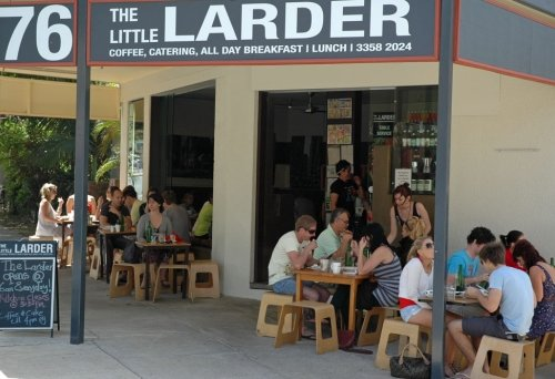 People sitting on stools on footpath having breakfast outside Little Larder Cafe in New Farm