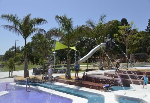 Playground equipmement and children playing in aquativity area of River Heart Parklands Ipswich
