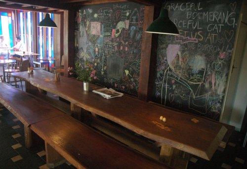 Common table and blackbaord with graffiti on it inside the Burrow West End