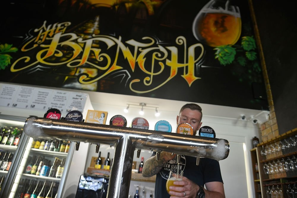 Barman pulling a beer from behind the bar inside The Bench Boutique Bar in Cleveland