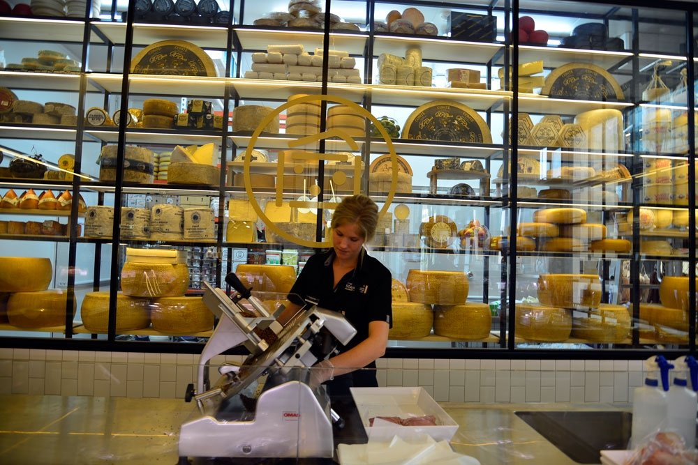 Woman cutting cheese behind counter at the Standard Market Company The Gasworks Newstead