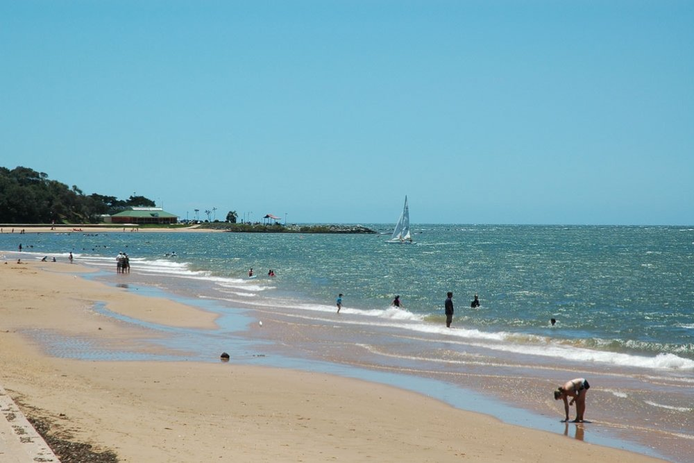 People swimming and walking on Suttons Beach Queensland
